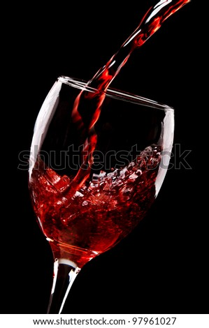 red wine pouring into wine glass isolated on a black background - stock photo