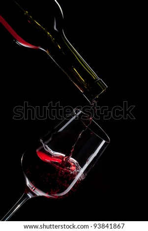 red wine pouring into wine glass isolated on black - stock photo