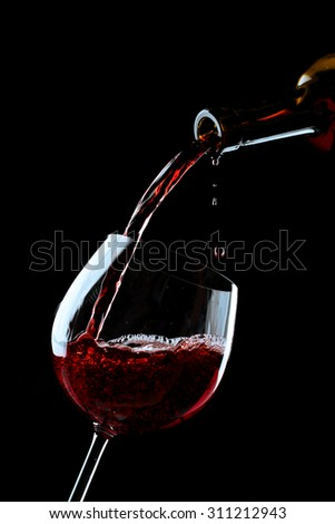 Red wine pouring into wine glass on black background - stock photo