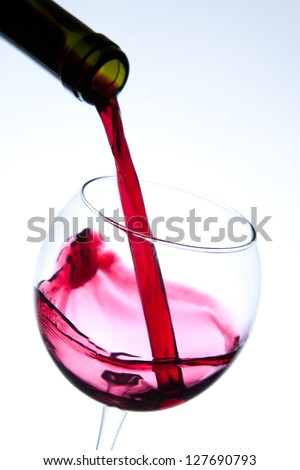 Red wine pouring into wine glass. Studio shot on white background. - stock photo