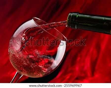 Red wine pouring on red background - stock photo