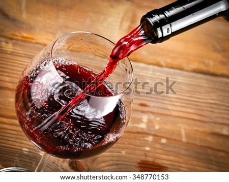 Red wine pouring on wood background - stock photo