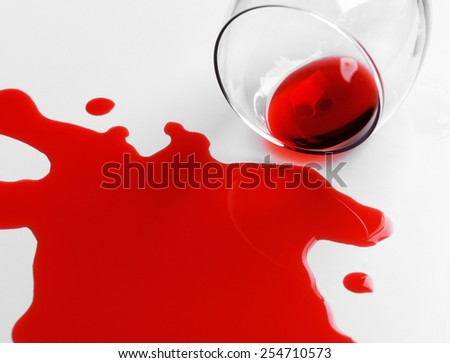 Red wine spilled from glass on white background - stock photo