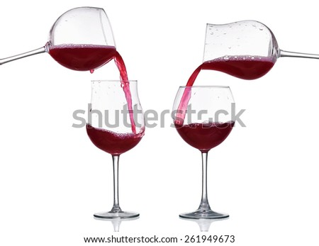 Red wine splash in the glass, pouring from a wineglass isolated on white - stock photo