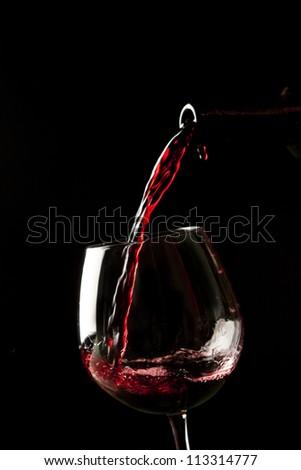 Red wine splash on a glass on black background. - stock photo