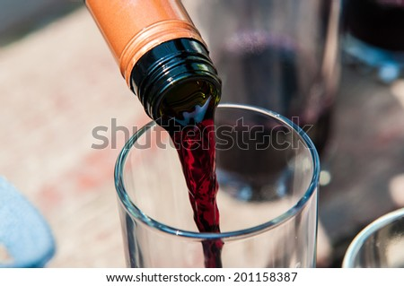 Red wine stream from bottle to glass - stock photo