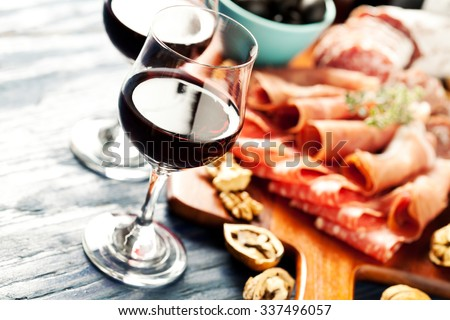 Red wine with charcuterie assortment on the background - stock photo