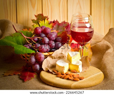 Red wine with cheese, almonds and grapes on sackcloth on a background of a wooden wall and autumn leaves - stock photo