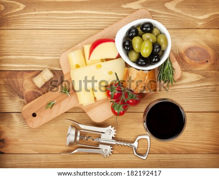 Red wine with cheese, bread, olives and spices. Over wooden table background. View from above - stock photo