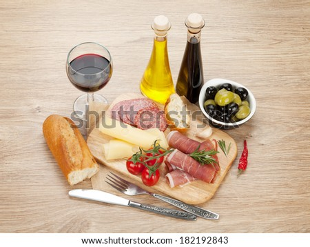 Red wine with cheese, olives, tomatoes, prosciutto, bread and spices. Over wooden table background - stock photo