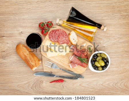 Red wine with cheese, olives, tomatoes, prosciutto, bread and spices. Over wooden table background. View from above with copy space - stock photo