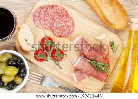 Red wine with cheese, prosciutto, bread, vegetables and spices on wooden table - stock photo