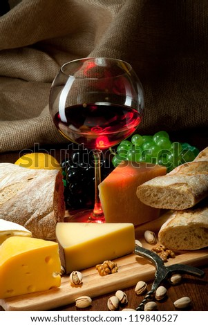 Red wine with cheeses, bread and fruits - stock photo