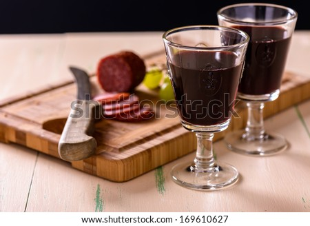 Red wine with salami and grapes on old wood table and some grapes on the side - stock photo