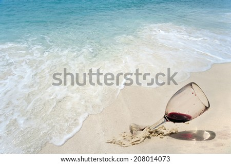 Red wineglasses on the sand - stock photo