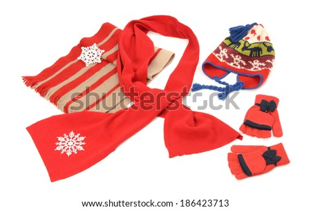 Red winter accessories nicely arranged. Wool scarves, a pair of gloves and a hat isolated on white background. - stock photo