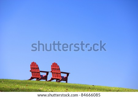 Red wooden Adirondack style chairs are sitting on a green grassy hillside. Horizontal shot. - stock photo