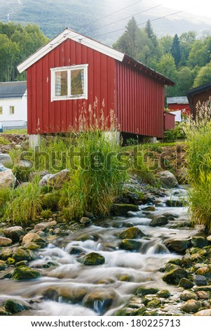 Red wooden cabin at campsite near small mountain river, Norway - stock photo