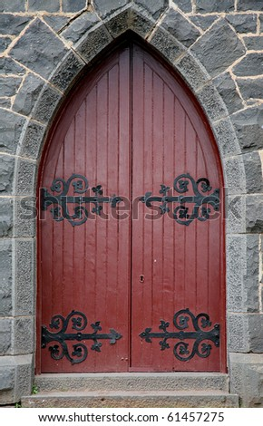 red wooden church door with blue stone surround - stock photo
