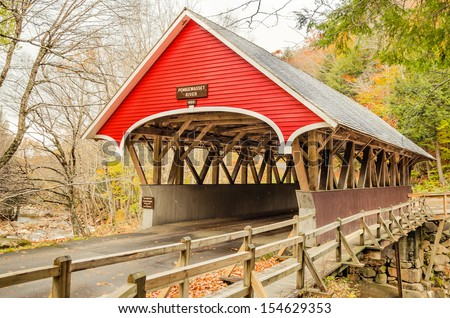 Red Wooden Covered Bridge in Autumn and Cloudy Sky - stock photo