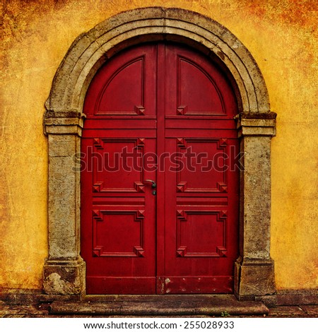Red wooden door, renaissance style, Europe. Architectural theme. Photo in retro style. Paper texture. Aged textured photo in retro style  - stock photo