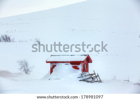 Red wooden Finnish house covered with snow - stock photo