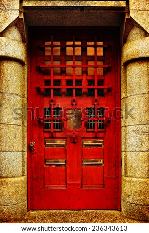 Red wooden glass door of a stone classical building, Europe. Architectural theme. Photo in retro style. Paper texture. Aged textured photo in retro style  - stock photo