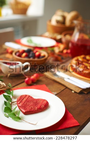 Red wooden heart and green branch on plate with traditional food on background - stock photo