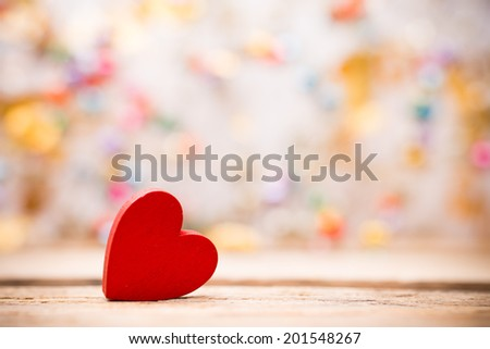 Red wooden heart on a wooden background with bokeh background. - stock photo