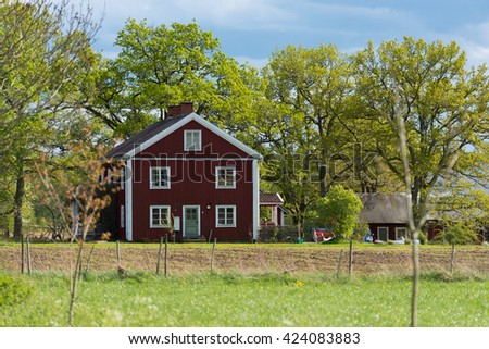 Red wooden house in Sweden. Old, traditional farmhouse from the 18th century in central Smaland on a sunny day in spring - stock photo