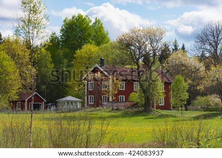 Red wooden house in Sweden. Old, traditional farmhouse from the 19th century in central Smaland on a sunny day in spring - stock photo