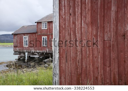 Red wooden house worn by sea and weathers, standing at Helgeland coast in Norway.  - stock photo