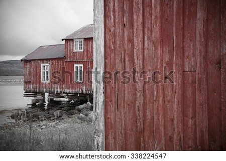 Red wooden house worn by sea and weathers, standing at Helgeland coast in Norway. Desaturated, lens vignetting applied.  - stock photo