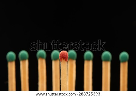 Red wooden match standing in front of defocused set of eight green matches, isolated on black background - stock photo