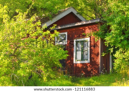 Red wooden part of summerhouse in Sweden - Surrounded in green foliage - stock photo
