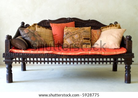 Red wooden sofa chair with cushions - stock photo
