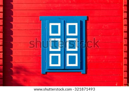 Red wooden wall with a colorful shutters. Lithuania. - stock photo