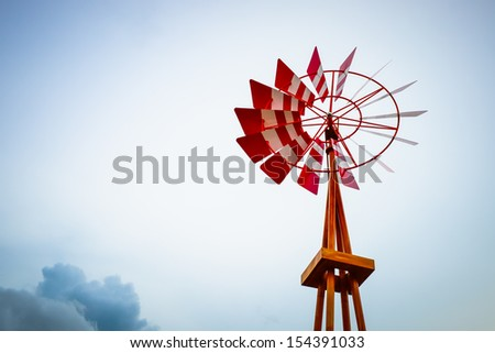 Red wooden Wind turbines with in the sunset - stock photo
