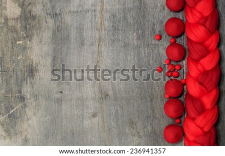 red wool for felting and place for text on wooden background - stock photo
