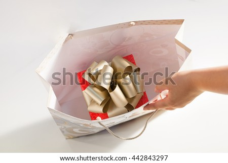 Red wrap gold ribbon bow gift box present inside paper bag hand christmas birthday isolated - stock photo