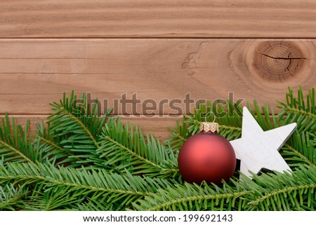 Red xmas bauble lying on fir - stock photo