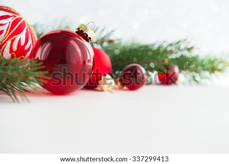 Red xmas ornaments and xmas tree on white wooden background. Merry christmas card. Winter holidays. Xmas theme. Happy New Year. - stock photo