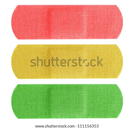 Red, yellow and green color bandaids or bandages isolated on white background. - stock photo