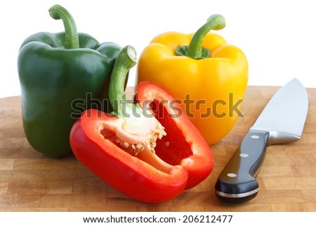Red, yellow and green peppers on chopping board. With knife and cut red pepper. - stock photo
