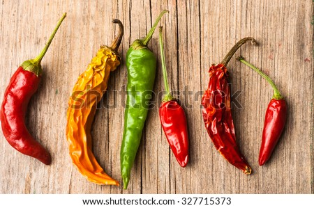 Red, yellow and green peppers on the wooden background - stock photo