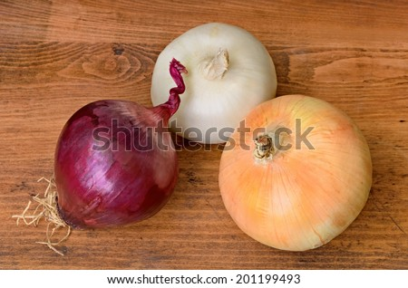 Red, Yellow and Red Sweet Onions on Wood - stock photo