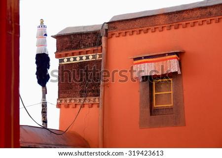 Reddish walls and buddhist flagpole-paint splattered window in the Tashilhunpo-Heap of Glory buddhist monast.-seat of Panchen Lama. Shigatse.at the Yarlung Tsangpo and Nyang Chu rivers junction-Tibet. - stock photo