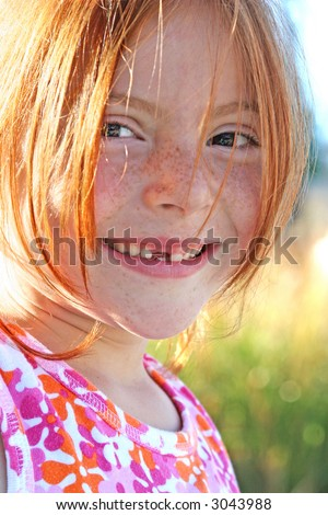 Redhead backlit by the sun - stock photo