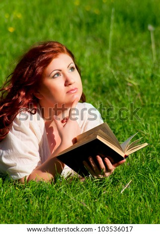 redhead beautiful girl reading a book in nature lying on the grass - stock photo