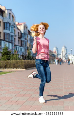 Redhead beautiful young woman jumping high in air over blue sky holding colorful lollipop. Pretty girl having fun outdoors - stock photo
